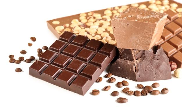 Barres de chocolat aux noisettes et grains de café isolés sur blanc