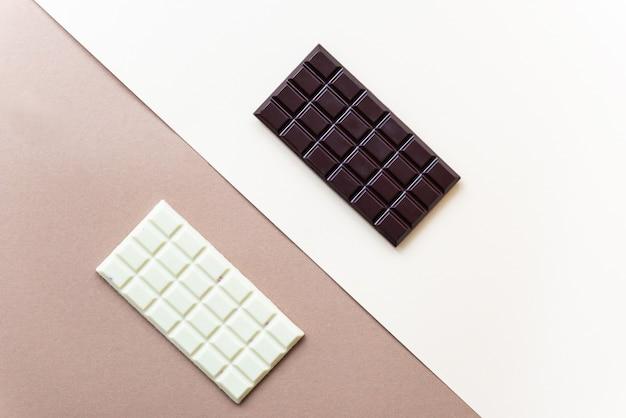 Barres de chocolat blanc et noir sur fond marron.