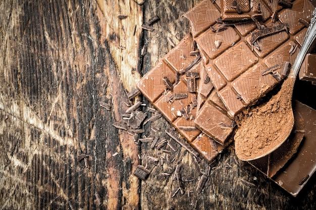 Barres de chocolat avec du cacao en poudre sur table en bois.