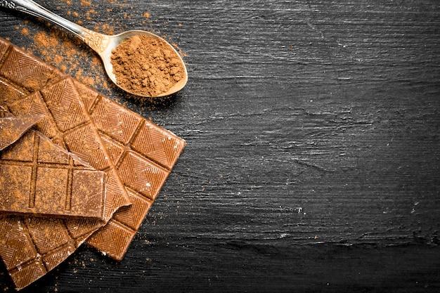Barres de chocolat avec du cacao en poudre sur tableau noir.