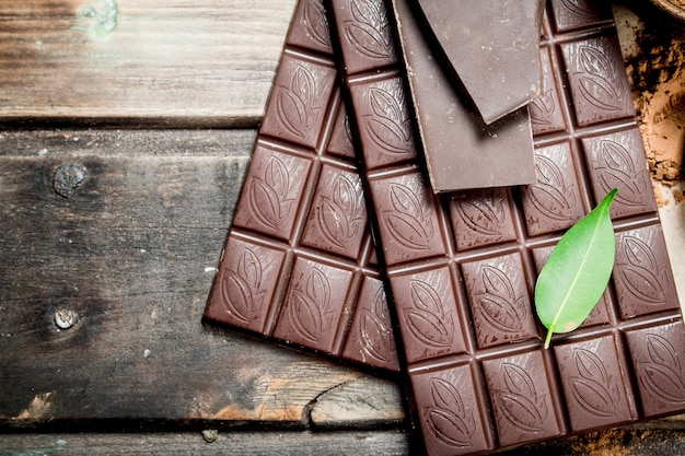 Barres de chocolat à la feuille verte. sur un fond en bois.