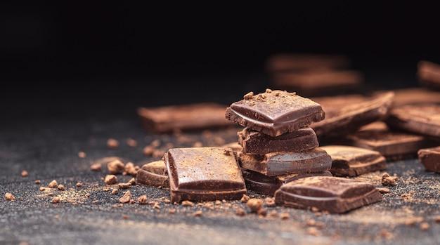Barres de chocolat sur fond d'ardoise noire avec de la poudre de cacao, pile de morceaux de chocolat noir