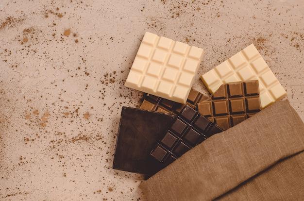 Barres de chocolat noir, lait et blanc sur table en bois. vue de dessus avec espace copie