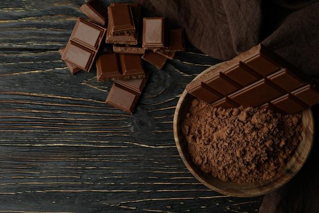 Barres de chocolat savoureuses et poudre sur table en bois