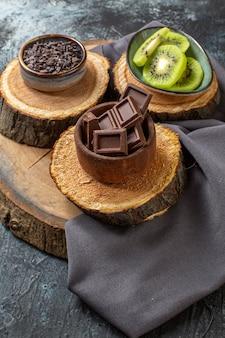 Barres de chocolat vue de face avec des kiwis tranchés sur une surface gris foncé