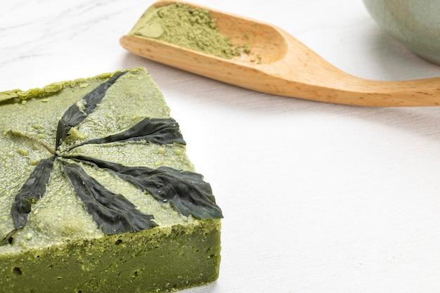 Barres de délicieux gâteau au chocolat blanc au cannabis matcha et thé vert puissant sur une table.