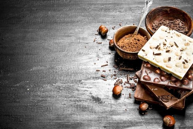 Barres de différents types de chocolat avec du cacao en poudre. sur le tableau noir.