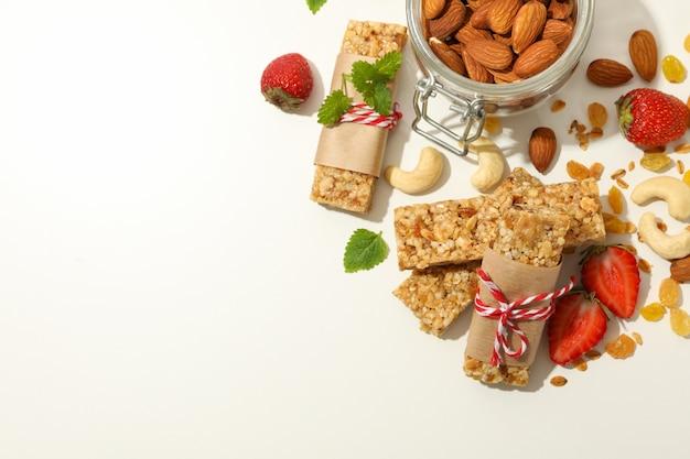 Barres granola, fraises et noix sur fond blanc, espace pour le texte