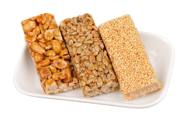 Barres de miel aux arachides, graines de sésame et de tournesol isolés