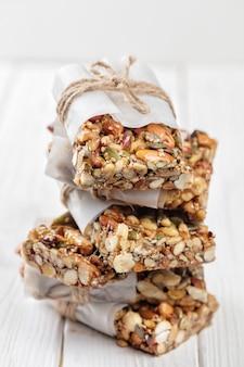 Barres de petit déjeuner superfood faites maison avec des noix grillées comme amande, noix de cajou, graines de citrouille, graines de sésame, miel