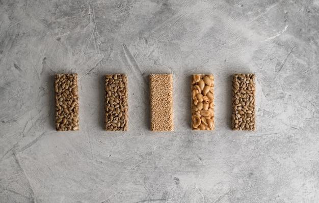 Barres de remise en forme naturelle douce avec des noix et des céréales sur fond gris