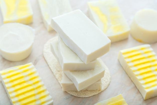 Barres de savon aux olives naturelles. de nombreux savons blancs faits maison. savon coloré jaune fait à la main, produits de bain spa pour les soins de la peau du corps. produits d'hygiène.