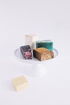 Des barres de savon colorées sur un gâteau se tiennent sur fond blanc