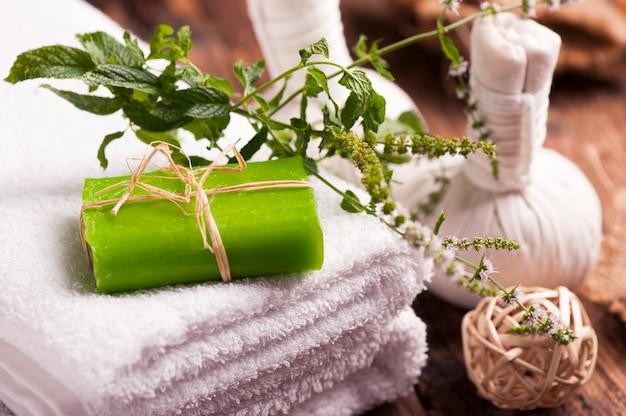Barres de savon avec feuilles de menthe fraîche et serviettes sur table en bois