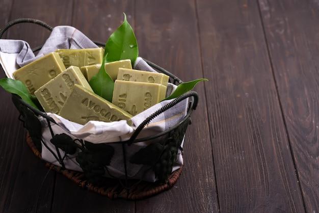 Barres de savons à l'huile d'olive naturelle verte avec des feuilles vertes dans un panier en bois foncé