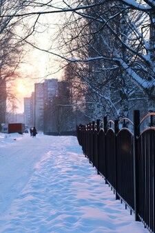 Barrière de fer de paysage d'hiver au coucher du soleil