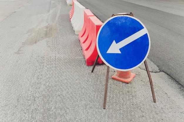 Barrière en plastique rouge-blanc sur la route, sécurité routière avec restrictions.