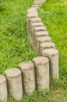 Barrière de poteau en pierre basse sur l'herbe verte en flou