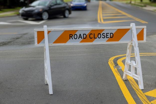 Barrière de rue de couleur rouge et blanche sur une route vide route fermée par des barrières bloquant l'accès