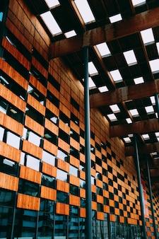 Bas affichage angle, de, a, bâtiment moderne, à, murs bois, et, fenêtres bleues, sous, lampe blanche, lumières