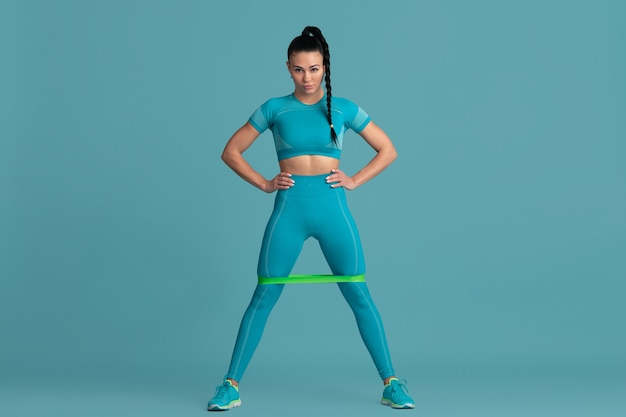 Bas du corps. belle jeune athlète féminine pratiquant, portrait bleu monochrome. modèle brune de coupe sportive avec élastiques. musculation, mode de vie sain, concept de beauté et d'action.