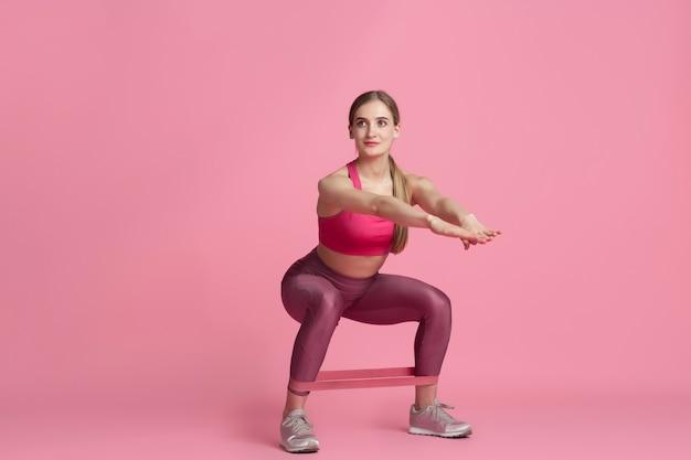 Bas du corps. belle jeune athlète féminine pratiquant, portrait rose monochrome. modèle caucasien de coupe sportive avec élastiques. musculation, mode de vie sain, concept de beauté et d'action.