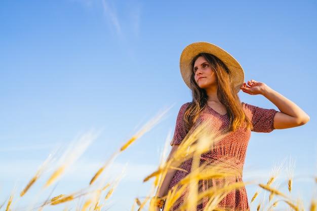 D'en bas une jeune femme en robe à pois touchant un chapeau de paille et regardant ailleurs en se tenant debout au milieu d'épillets contre le ciel bleu dans un champ de blé en été