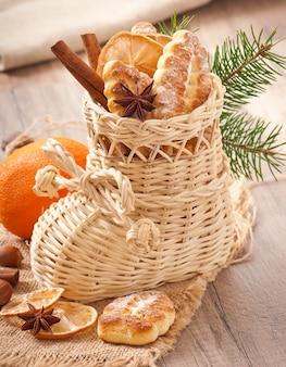 Bas de noël en osier rempli de biscuits, bâtons de cannelle, citron confit et anis étoilé