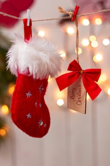 Un bas de noël rouge et une note en bois avec un arc rouge avec du texte joyeux noël sur des pinces à linge