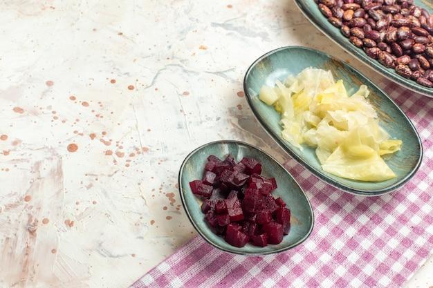 Bas vue rapprochée haricots chou mariné betterave coupée sur assiettes ovales torchon à carreaux violet et blanc sur table gris clair