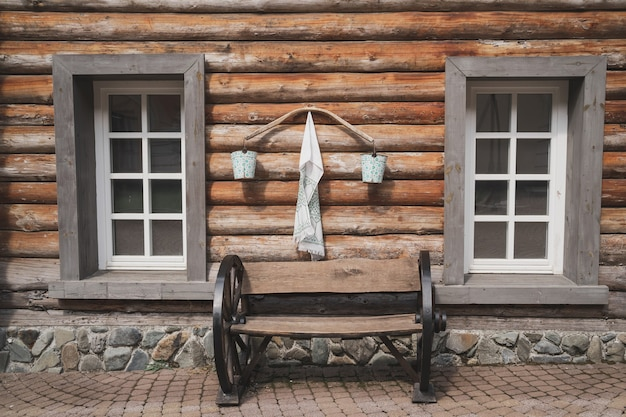 Bascule de village avec seaux dans la maison de village faite de barres avec banc de fenêtres classique à la v...
