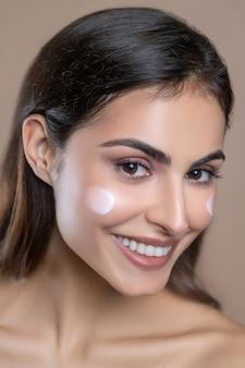 Base du maquillage. gros plan du visage de la belle jeune femme heureuse aux cheveux noirs et au regard expressif avec de la crème sur la joue