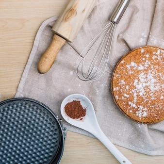 Base de gâteau fait maison avec de la poudre de chocolat; rouleau à pâtisserie; fouet et récipient de cuisson sur la table