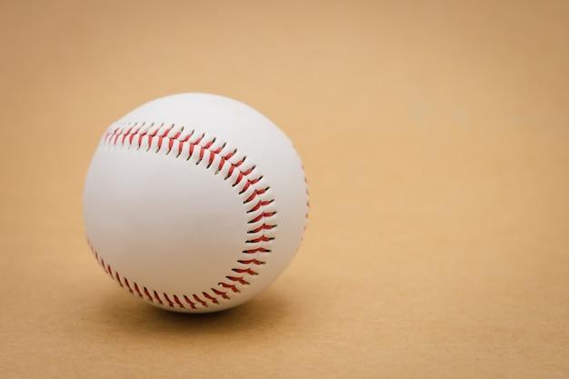 Baseball isolé sur un fond marron et baseball à couture rouge. baseball blanc