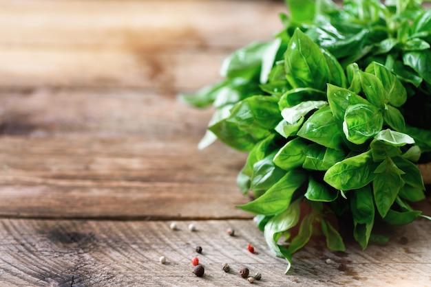 Basilic bio frais vert sur bois avec fond.