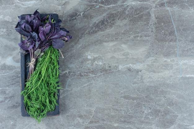Basilic violet et aneth sur plateau , sur la table en marbre.