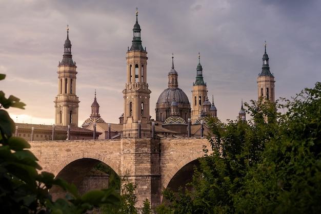 Basilique cathédrale de notre-dame du pilier avec pont et arbres au coucher du soleil. une église catholique romaine dans le vieux centre-ville de saragosse. monument historique de la région d'aragon au nord de l'espagne