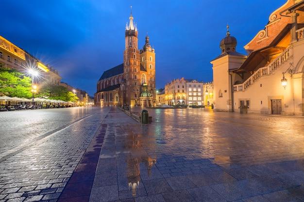 Basilique de saint mary sur la place du marché médiéval dans la vieille ville sur la nuit pluvieuse, cracovie