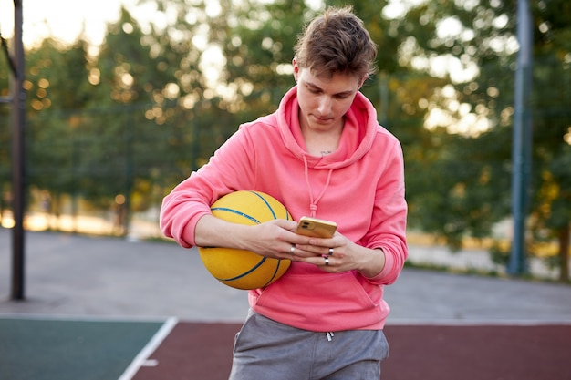 Basket-ball adolescent garçon discutant avec un ami pendant qu'il a du temps libre après le match