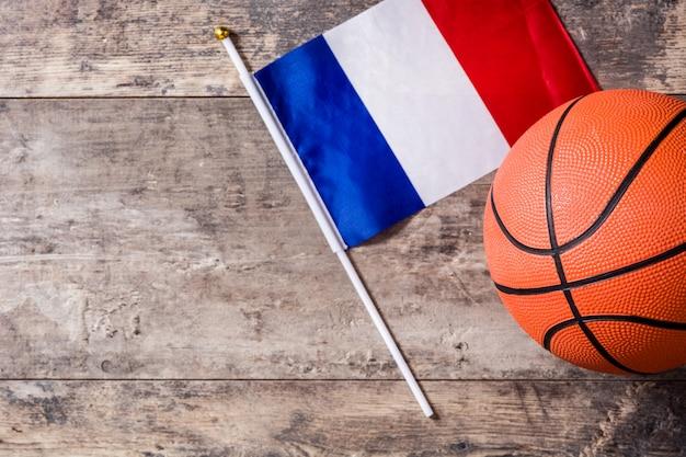 Basket-ball et drapeau français sur table en bois