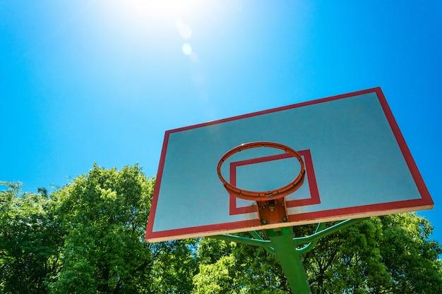 Basket-ball et panneau arrière avec ciel bleu