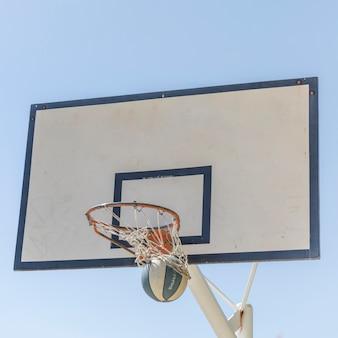 Basketball traversant le cerceau contre le ciel clair