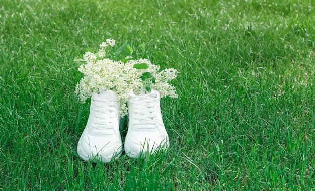 En baskets blanches branches fleuries de cerisier blanc bonjour été copiez l'espace