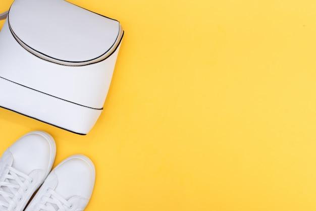 Baskets blanches femelles et jeans sur fond jaune avec espace de copie.