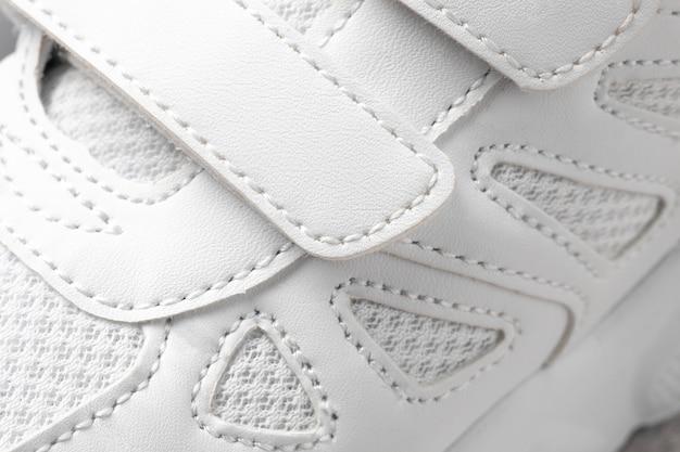 Baskets blanches fermoirs en gros plan d'en haut photo macro d'une basket de sport pour enfants en cuir...