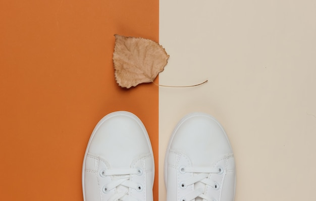Baskets blanches avec une feuille d'automne sèche sur papier de couleur
