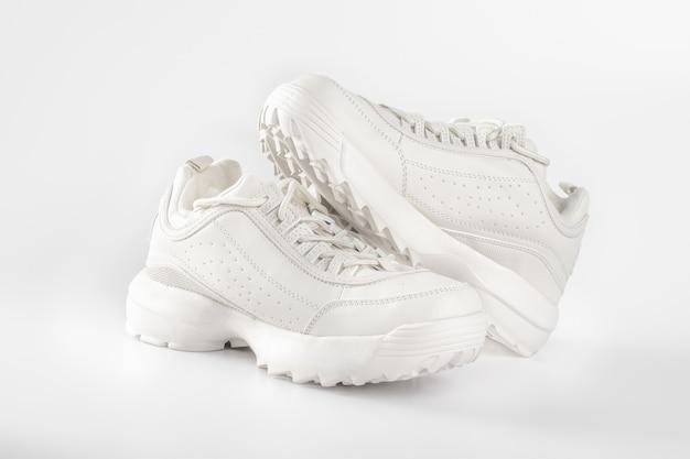Baskets blanches sur fond blanc paire de baskets pour femmes à la mode sur les chaussures de sport blanc concept de chaussures de sport