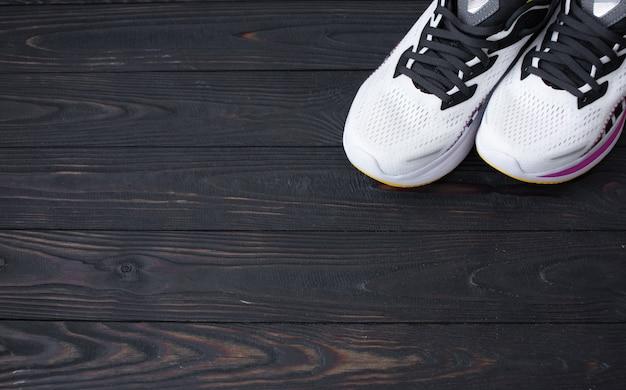 Baskets blanches sur fond en bois avec espace de copie
