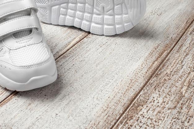 Baskets blanches sur fond clair avec un endroit pour copier du texte ou concevoir une paire d'enfant à la mode...
