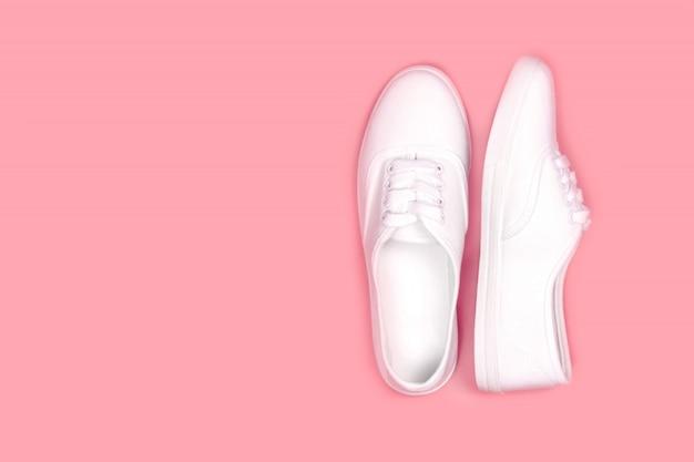 Baskets blanches sur fond rose